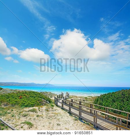 Boardwalk To The Beach Under Clouds