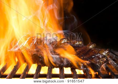 Ribs on barbecue grill in flames