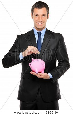 A Businessman Putting A Coin Into A Pink Piggy Bank