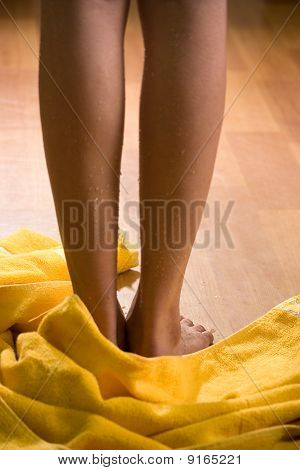 Wet female legs with towel on wooden floor