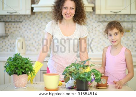 Happy mother and daughter with houseplants in the kitchen