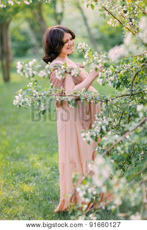 Beautiful pregnant woman in the flowering park
