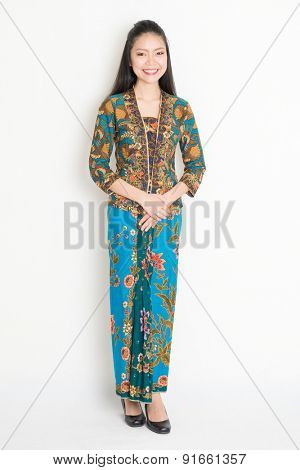 Full length Southeast Asian girl in batik dress standing on plain background.