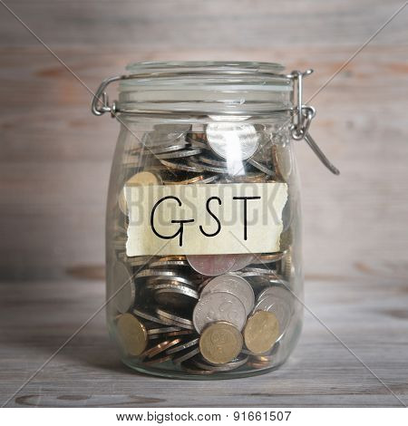 Coins in glass money jar with gst label, financial concept. Vintage wooden background with dramatic light.