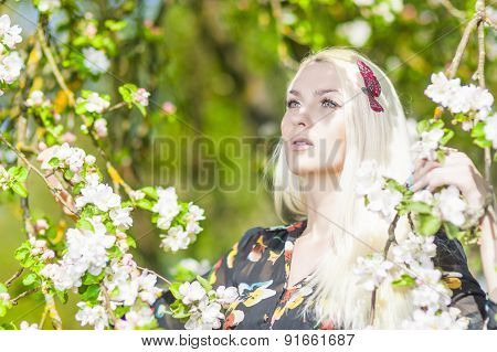 Beauty Concept:portrait Of Beautiful Blond Female Standing In Park By Blooming Tree And Relaxing