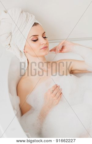 beautiful sexy girl long hair in the bathroom with foam  a towel on her head