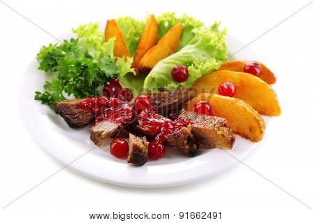 Beef with cranberry sauce, roasted potato slices on plate, isolated on white