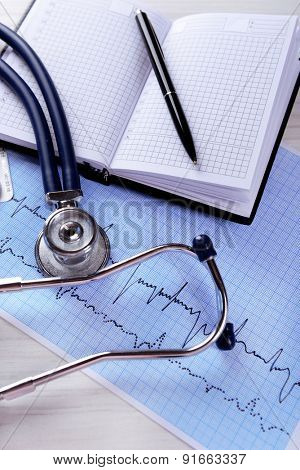 Cardiogram with stethoscope on table, closeup