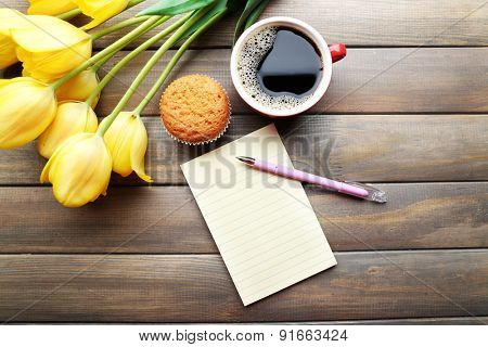 Cup of coffee with fresh cupcake, tulips and blank sheet of paper on wooden background