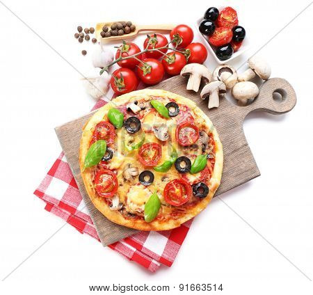 Tasty pizza with vegetables and basil on cutting board isolated on white
