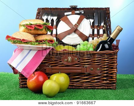 Wicker picnic basket with tablecloth and food on green grass on blue background