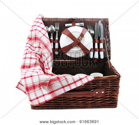 Wicker picnic basket with tableware and tablecloth isolated on white