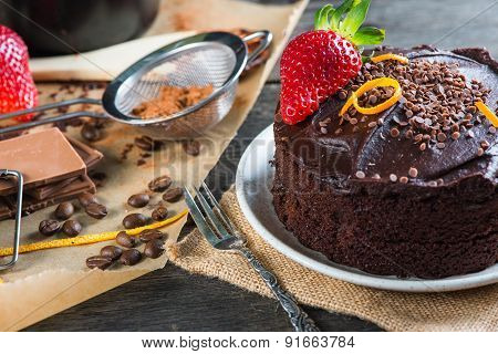 Serving Decorated Dark Chocolate Cake On Wooden Table