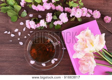 Cup of herbal tea with pink roses on wooden table, top view