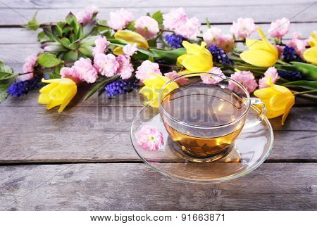 Cup of herbal tea with flowers on wooden background
