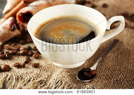 Cup of coffee with beans on table, closeup