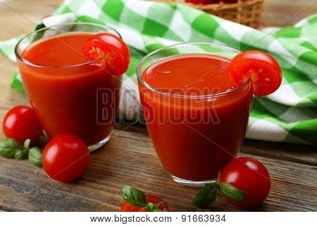 Glasses of tomato juice with vegetables on table close up