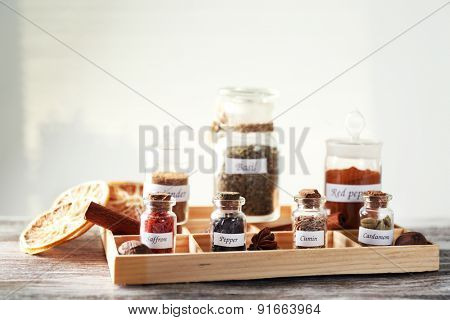 Assortment of spices in glass bottles in box, on light background