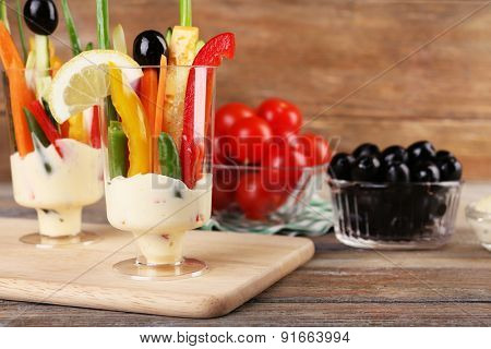Snack of vegetables in glassware on wooden background