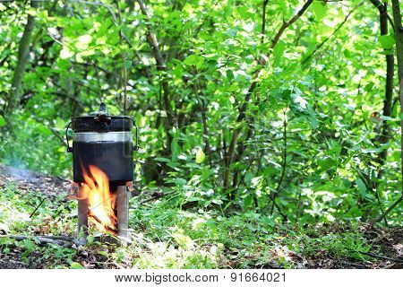Tourist kettle above fire in park