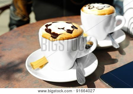 Cups of cappuccino on table in cafe