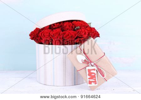 Bouquet of red roses in textile box with present on wooden background