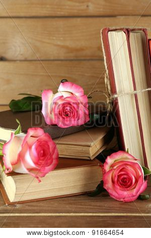 Tied books with pink roses on wooden background