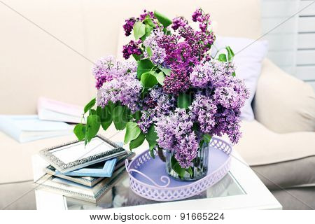 Beautiful lilac flowers in vase on table of interior background