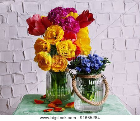 Beautiful flowers in vases on wall background