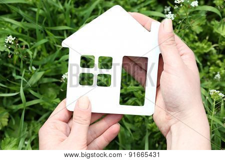 Female hands holding toy house outdoors