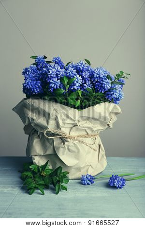 Beautiful bouquet of muscari - hyacinth in vase on gray background