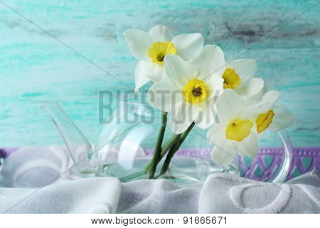 Fresh narcissus flowers in tray with fabric on wooden background