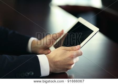 Businessman working with tablet at wooden table, closeup