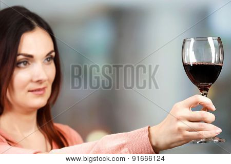 Young woman tasting wine on bright background