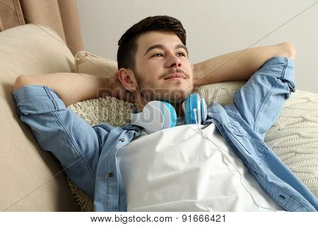 Handsome young man with headphones lying on sofa in room