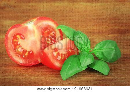 Tomato and basil on wooden background