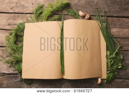Open recipe book with fresh herbs and spices on wooden background