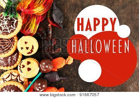 Different sweets for Halloween party on dark background