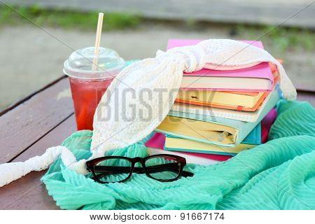 Books, glasses, swimsuit and drink outdoors