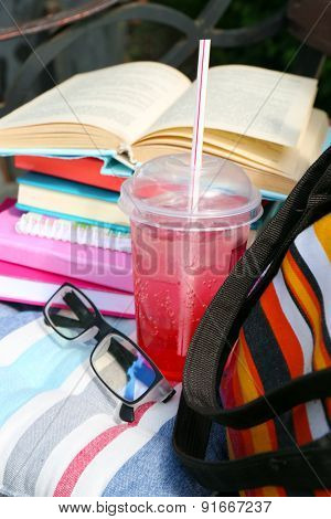 Books, glasses, drink and bag on bench outdoors