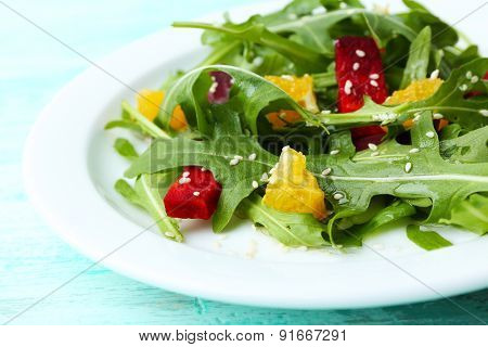 Tasty salad with arugula leaves in plate on wooden table, closeup