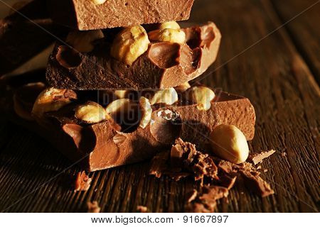 Stack of chocolate with nuts on wooden table, closeup