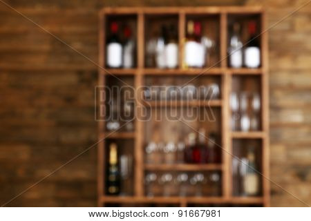 Abstract blurred view of shelving with wine bottles with glasses on wooden wall background