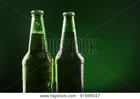 Glass bottles of beer on dark green background