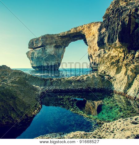 Azure Window, famous stone arch on Gozo island with reflection, Malta. Toned photo