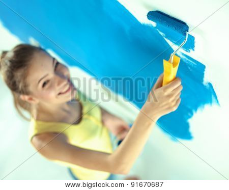 Beautiful young woman doing wall painting .