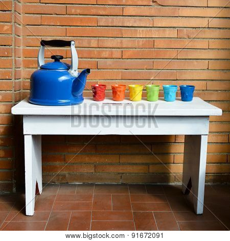 Blue kettle and multicolored cups are on the bench against brick wall. Ready to tea-drinking. Home-style.