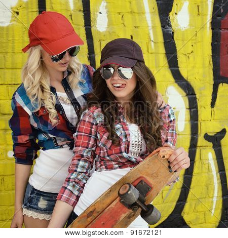 Two teen girl friends having fun together with skate board. Outdoors, urban lifestyle.