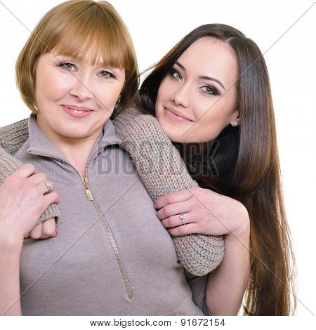 Portrait of young daughter embracing her mother, happy smiling, over white