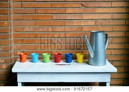 watering-pot and multicolored flower-pots are on the bench against brick wall. Home-style. Gardening.